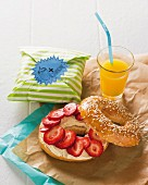 A cream cheese bagel with strawberries