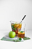 Apple and mint iced tea in a glass and in a jug