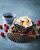 A brownie cupcake with a meringue topping and raspberries