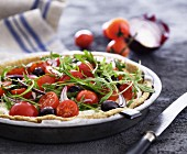 Goat's cheese tart with tomatoes, rocket, onions and olives