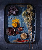 Dried herbs and spices on a blue tray