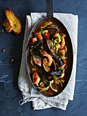 Bouillabaisse in a pan with garlic bread