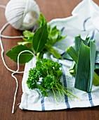 Fresh herbs and leek on a tea towel