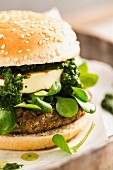 A vegetarian burger with a bean patty, chimi-churri, halloumi and lamb's lettuce