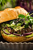 Hamburger with lamb, guacamole, onions, cheese and various bean sprouts