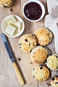 Scones with jam and butter on a wooden table with a cloth