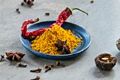 Turmeric powder, a dried chilli pepper, shiitake mushrooms and star anise on a plate and next to it