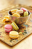 Colourful macaroons in a metal bowl on a tray
