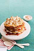 A stack of pancakes with jam and meringue