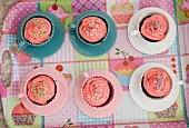 Pink cupcakes with birthday candles served in cups