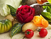 A carved beetroot rose, carrot flower and various types of vegetables