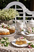 Apple cake with meringue topping, coffee service and opulent bouquet of lily-of-the-valley on sunny table outdoors