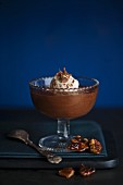 Dark chocolate mousse in a dessert glass with whipped cream, chocolate shavings and a pecan brittle