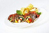 Beef roulade filled with vegetables, tomato sauce and grilled corn cobs