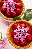 Strawberry tartlets decorated with lilac blossoms