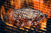 A ribeye steak on a flaming barbecue