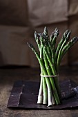 A bunch of green asparagus on a rustic surface