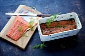 Graved lax being made: marinated salmon fillets in a rectangular container with spices and dill and on a chopping board