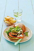 A burger with tomatoes, aubergines and avocado cream