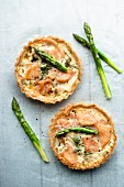 Two asapragus and smoked salmon tartlets with asparagus spears (seen from above)