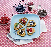 Heart-shaped waffles with berries, jam, chocolate and cream