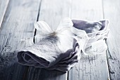 Grey linen napkin tied with white ribbon on wooden surface