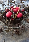 A baking tin with red Christmas tree baubles, hawthorn berries, alderberry sprigs and maple berry sprigs