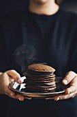 A woman holding a stack of orange and cocoa pancakes