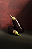 Two aubergines against a dark background