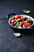 Oven-roasted tomatoes with olives, garlic cloves and basil