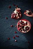 A pomegranate on a black slate platter