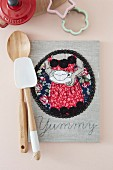 Hand-made cookery book with decorative motif on linen cover, wooden spoon and spatula