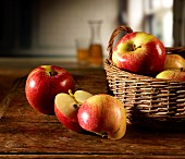 Red apples in a basket on a wooden table, one apple sliced
