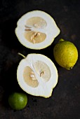 A halved citron next to a lemon and a lime