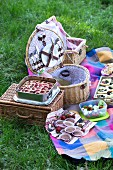 A summer picnic with strawberry cake, muffins, salad and drinks