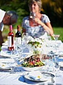 A set table with roast pork, salad and wine for a summer party