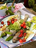 Grilled fish in vine leaves, grilled tomatoes and grilled lemons