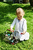 A little girl playing with cherries in a garden