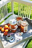 Jars of homemade apricot syrup on a wooden tray in a garden