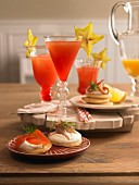 Blinis with smoked fish and Campari cocktails