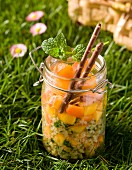 Sweet tabbouleh with peaches and oranges in a jar on a field