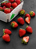 Fresh strawberries in a cardboard punnet and next to it