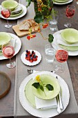 A table laid in a garden with white and pastel green crockery