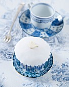 A white cupcake decorated with a fondant bird