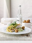 Zander fillet with a herb and potato crust on creamy fennel salad with crispy olives