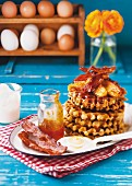 Almond and yoghurt waffles with bananas, orange syrup and crispy bacon