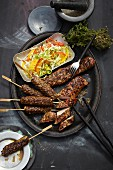 Grilled pork fillet, oriental minced meat kebabs and pointed cabbage salad