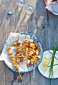 Grilled chicken kebabs with pineapple and lemongrass, sweetcorn and sheep's cheese