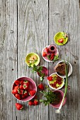 An arrangement of ingredients for various strawberry dishes on a wooden surface