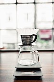 A glass coffee jug with a filter on the counter in coffee shop
